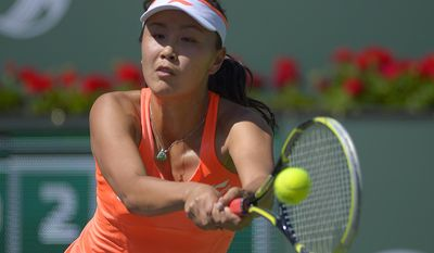 Peng Shuai, of China, returns a shot against Vera Zvonareva, of Russia, during a first round match at the BNP Paribas Open tennis tournament, Wednesday, March 5, 2014, in Indian Wells, Calif. (AP Photo/Mark J. Terrill)