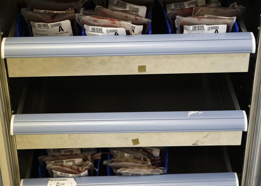 In this Tuesday, March 4, 2014 photo, shelves containing units blood are seen in storage at the Central Illinois Community Blood Center in Springfield, Ill. The blood center says they are running around 70 percent of where they should be after a cold winter is suspected of detracting donors.  (AP Photo/The State Journal-Register, Justin L. Fowler)