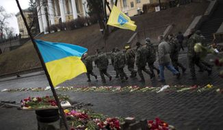 "Ukrainian men wearing camouflage uniforms march along a street at a memorial for people killed during clashes with police at Kiev's Independence Square, Ukraine, Wednesday, March 5, 2014. Stepping back from the brink of war, Vladimir Putin talked tough but cooled tensions in the Ukraine crisis Tuesday, saying Russia has no intention ""to fight the Ukrainian people"" but reserves the right to use force. As the Russian president held court in his personal residence, U.S. Secretary of State John Kerry met with Kiev's fledgling government and urged Putin to stand down. (AP Photo/Emilio Morenatti)"