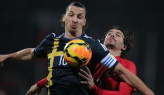 Turkey's Ersan Gulum, rear, vies with Sweden's Zlatan Ibrahimovic during their International Friendly soccer match at 19 Mayis Stadium in Ankara, Turkey, Wednesday, March 5, 2014.(AP Photo)