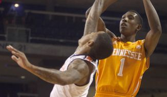 Tennessee Volunteers guard Josh Richardson (1) hits a jump shot over Auburn Tigers guard Chris Denson (3) during the first half of the NCAA men's basketball game on Wednesday, March 5, 2014, at Auburn Arena in Auburn, Ala. (AP Photo/Opelika-Auburn News/Albert Cesare)