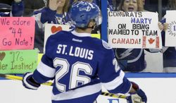 FILE - In this Feb. 6, 2014 file photo, a fan holds up a sign congratulating Tampa Bay Lightning right winger Martin St. Louis (26) for being selected to the Canadian Olympic hockey team before an NHL hockey game against the Toronto Maple Leafs, in Tampa, Fla. The New York Rangers and Lightning are pulling off the first major deal on NHL trade deadline day, Wednesday, March 5, 2014, swapping captains Ryan Callahan and Martin St. Louis. (AP Photo/Chris O'Meara, F