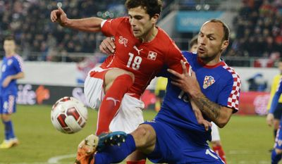 Switzerland's Admir Mehmedi, left, and Croatia's Gordon Schildenfeld, right,  challenge  for the ball during a  friendly  soccer match between Switzerland and Croatia at the AFG Arena in St. Gallen, Switzerland, Wednesday, March 5, 2014. (AP Photo/Keystone,Steffen Schmidt)