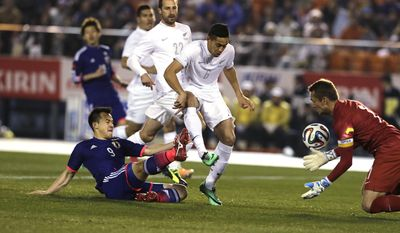 Japan's Shinji Okazaki, bottom left, shoots to score as New Zealand's goalkeeper Glen Moss, right, tries to save the ball during their Kirin Challenge Cup international friendly soccer match at the National Stadium in Tokyo, Wednesday, March 5, 2014. (AP Photo/Shuji Kajiyama)