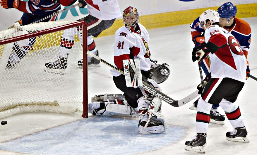 Ottawa Senators goalie Craig Anderson (41) watches the puck go in the net as Erik Karlsson (65) and Edmonton Oilers' Taylor Hall (4) battle in front during the second period of an NHL hockey game, Tuesday, March 4, 2014 in Edmonton, Alberta. (AP Photo/The Canadian Press, Jason Franson)