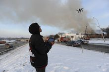 Sanford Miles pilots a drone to shoot video of a large fire at an apartment building in Detroit, Wednesday, March 5, 2014. There were no immediate reports of any deaths caused by the fire at the Jason Manor Apartments, which broke out at about 6 a.m. Four people were taken to hospitals for treatment, Detroit Fire Commissioner Jonathan Jackson said. (AP Photo/Detroit News, David Coates)  DETROIT FREE PRESS OUT; HUFFINGTON POST OUT; MAGS OUT; MANDATORY CREDIT