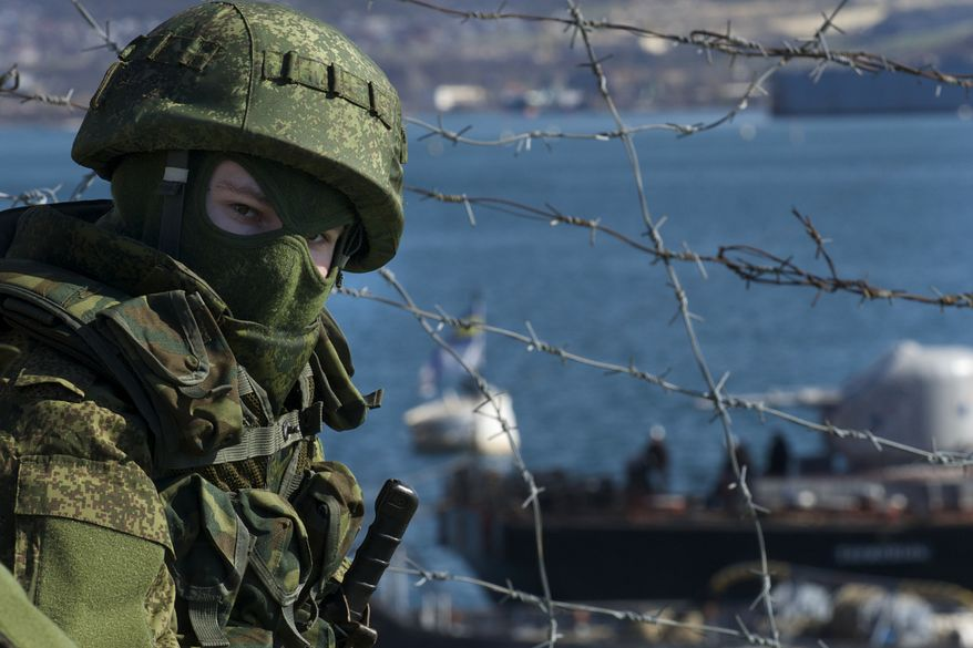 Russian soldiers guard a pier where two Ukrainian naval ships are moored, in Sevastopol, Ukraine, on Wednesday, March 5, 2014. (Associated Press) ** FILE **