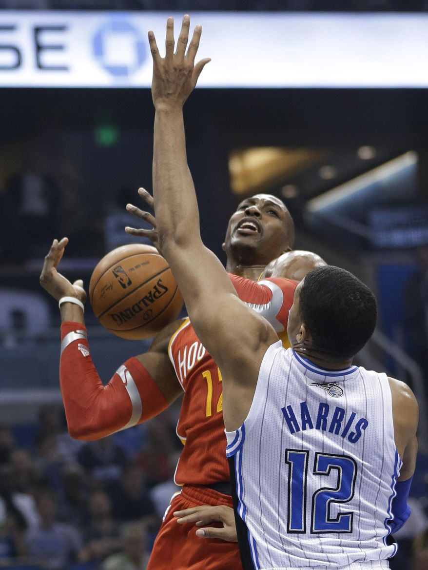 Orlando Magic's Tobias Harris (12) fouls Houston Rockets' Dwight Howard, left, who was going up for a shot during the first half of an NBA basketball game in Orlando, Fla., Wednesday, March 5, 2014. (AP Photo/John Raoux)