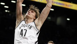 Brooklyn Nets small forward Andrei Kirilenko (47) scores in front of Memphis Grizzlies center Marc Gasol (33) in the first half of an NBA basketball game on Wednesday, March 5, 2014, in New York. (AP Photo/Paul J. Bereswill)