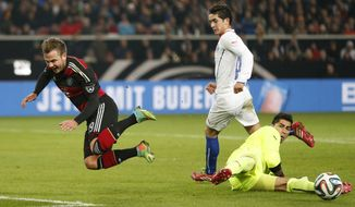 Germany's Mario Goetze, left, and Chile's Johnny Herrera challenge for the ball during their International friendly soccer match between Germany and Chile in Stuttgart, Germany, Wednesday, March 5, 2014. (AP Photo/Matthias Schrader)