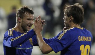 Andriy Yarmolenko, left, with his teammate Denys Garmash of Ukraine celebrate his goal against U.S. during an international friendly match at Antonis Papadopoulos stadium in southern city of Larnaca, Cyprus, Wednesday, March 5, 2014. The Ukrainians are facing the United States in a friendly in Cyprus, a match moved from Kharkiv, Ukraine, to Larnaca for security reasons. (AP Photo/Petros Karadjias)