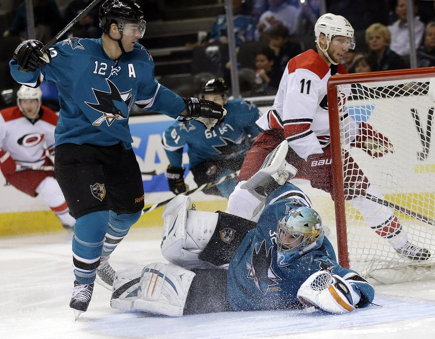 San Jose Sharks goalie Alex Stalock, bottom, stops a shot from Carolina Hurricanes' Jordan Staal (11) as Patrick Marleau (12) watches during the second period of an NHL hockey game on Tuesday, March 4, 2014, in San Jose, Calif. (AP Photo/Marcio Jose Sanchez)