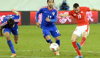 Swiss Josip Drmic , right, scores the opening goal  during a  friendly soccer match between Switzerland and Croatia at the AFG Arena in St. Gallen, Switzerland, Wednesday, March 5, 2014. (AP Photo/Keystone,Walter Bieri)