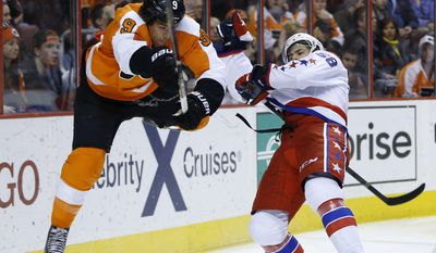 Philadelphia Flyers' Steve Downie, left, is sent flying after a collision with Washington Capitals' Connor Carrick during the second period of an NHL hockey game, Wednesday, March 5, 2014, in Philadelphia. (AP Photo/Matt Slocum)