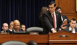 House Oversight and Government Reform Committee Chairman Rep. Darrell Issa, R-Calif., right, leaves as the committee's ranking member Rep. Elijah Cummings, D-Md., left, begins his statement on Capitol Hill in Washington, Wednesday, March 5, 2014, during the committee's hearing where former Internal Revenue Service (IRS) official Lois Lerner invoked her constitutional right not to incriminate herself. (AP Photo/Lauren Victoria Burke)