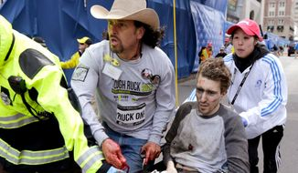 ** FILE ** Carlos Arredondo (left) rushed to help Jeff Bauman after the Boston Marathon bomb attack on April 15, 2013. (Associated Press)