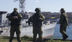 Russian soldiers guard a peer where two Ukrainian naval vessels are moored, in Sevastopol, Ukraine, on Wednesday, March 5, 2014. Ukraine's new prime minister said Wednesday that embattled Crimea must remain part of Ukraine, but may be granted more local powers. Since last weekend, Russian troops have taken control of much of the peninsula in the Black Sea, where Russian speakers are in the majority. (AP Photo/Ivan Sekretarev)