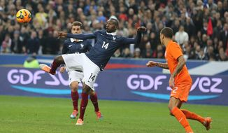 France's Blaise Matuidi, center, shoots to score the second goal for France, during the friendly soccer match between France and Netherlands at the Stade de France, in Saint Denis, north of Paris, Wednesday March 5, 2014.(AP Photo/Remy de la Mauviniere)