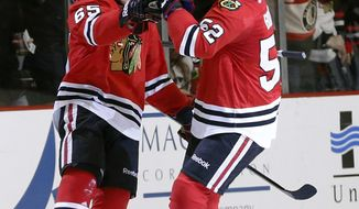 Chicago Blackhawks center Andrew Shaw (65) celebrates his goal with Brandon Bollig (52) during the first period of an NHL hockey game against the Columbus Blue Jackets on Thursday, March 6, 2014, in Chicago. (AP Photo/Charles Rex Arbogast)
