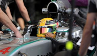 Formula One driver Lewis Hamilton of Mercedes sits in his car as he is pushed into the garage during pre-season testing at the Bahrain International Circuit in Sakhir, Bahrain, on Friday, Feb. 28, 2014. (AP Photo/Hasan Jamali)