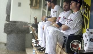 Minnesota Twins first baseman Joe Mauer, right, sits in the dugout with teammates during a heavy rain before a scheduled exhibition baseball game against the St. Louis Cardinals, Thursday, March 6, 2014, in Fort Myers, Fla. (AP Photo/Steven Senne)