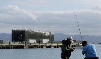 FILE - In this Tuesday, Oct. 29, 2013, file photo, two men fish in the water in front of a Google barge on Treasure Island in San Francisco. Google's mystery barge was floating Thursday, March 6, 2014,  toward its new home in the California delta after the Internet company was ordered to move it from San Francisco.  (AP Photo/Jeff Chiu, File)