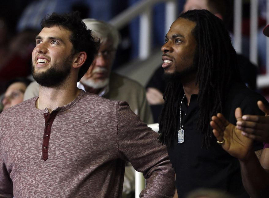 Indianapolis Colts quarterback Andrew Luck, left, and Seattle Seahawks cornerback Richard Sherman, both Stanford alumni, smile as they watch an NCAA college basketball game between Stanford and Colorado on Wednesday, March 5, 2014, in Stanford, Calif. Colorado won 59-56. (AP Photo/Marcio Jose Sanchez)