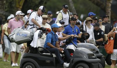 Tiger Woods, center, gets a ride in a cart with his caddy Joe LaCava, left, after play was suspended due to approaching inclement weather during the first round of the Cadillac Championship golf tournament, Thursday, March 6, 2014, in Doral, Fla. (AP Photo/Lynne Sladky)