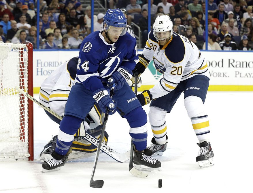 Tampa Bay Lightning right winger Ryan Callahan (24) picks up a loose puck in front of Buffalo Sabres defenseman Henrik Tallinder (20), of Sweden, during the second period of an NHL hockey game Thursday, March 6, 2014, in Tampa, Fla. (AP Photo/Chris O'Meara)
