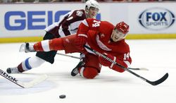 Detroit Red Wings' Gustav Nyquist (14), of Sweden, is knocked off his feet by Colorado Avalanche's Matt Duchene while trying to take a shot during the second period of an NHL hockey game Thursday, March 6, 2014, in Detroit. (AP Photo/Duane Burleson)