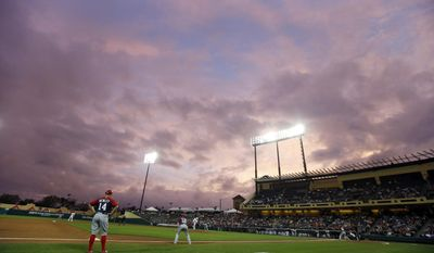 The sun sets beyond Champion Stadium in the second inning of an exhibition baseball game between the Washington Nationals and the Atlanta Braves, Thursday, March 6, 2014, in Kissimmee, Fla. (AP Photo/Alex Brandon)