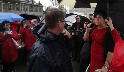 Washington Education Association President Kim Mead encourages some of the anticipated 300 teachers who descended on the Capitol, Thursday, March 6, 2014,  in Olympia, Wash., to voice their opposition to SB 5880 and HB 2800 bills. The legislation promotes mandates the use of state test scores in teacher evaluations, and which is vigorously opposed by the Washington Education Association. (AP Photo/The Olympian, Steve Bloom)