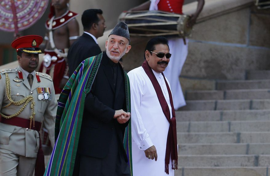 Sri Lankan President Mahinda Rajapaksa, right, and Afghan President Hamid Karzai walk together during an official reception for Karzai in Colombo, Sri Lanka, Thursday, March 6, 2014. Karzai is on a three-day official visit to Sri Lanka. (AP Photo/Eranga Jayawardena)