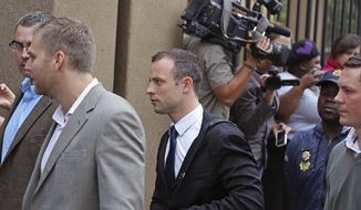 Oscar Pistorius, center, arrives at  the high court for the start of the fourth day of his trial in Pretoria, South Africa, Thursday, March 6, 2014. Pistorius is charged with murder in the shooting death of girlfriend Reeva Steenkamp in the pre-dawn hours of Valentine's Day 2013. (AP Photo/Schalk van Zuydam)