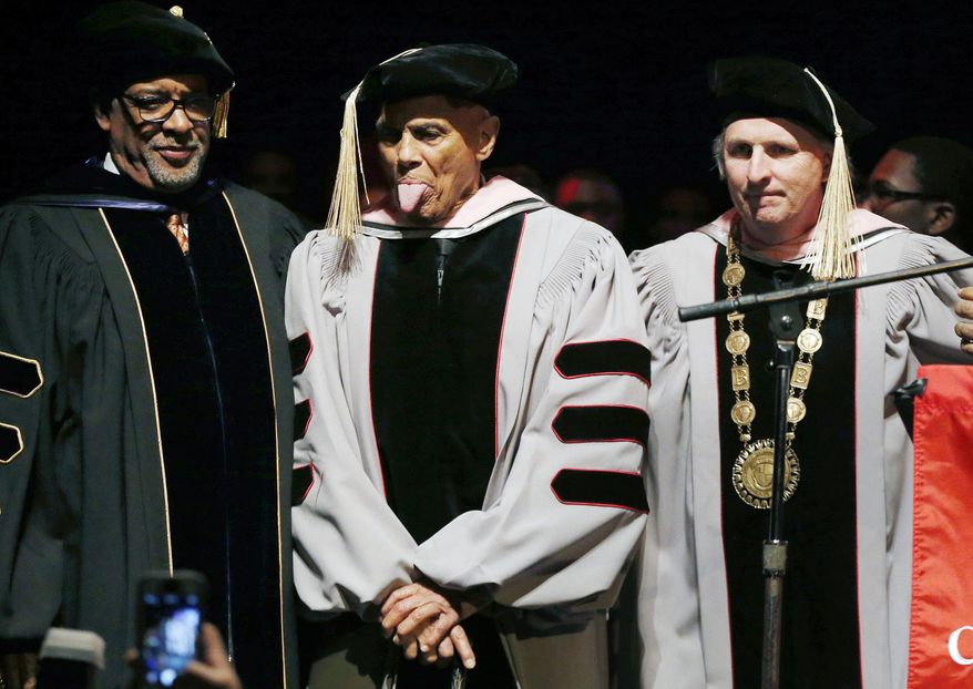 Harry Belafonte, second from left,  playfully sticks out his tongue after receiving an honorary doctor of music degree from Berklee College of Music President Roger H. Brown, right, at the Berklee Performance Center in Boston, Thursday, March 6, 2014. (AP Photo/Michael Dwyer)