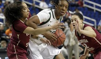 Miami's Keyona Hayes, center, is trapped by Florida State's Brittany Brown, right, and Nigia Greene, right, during the first half of an NCAA college basketball game at the Atlantic Coast Conference tournament in Greensboro, N.C., Thursday, March 6, 2014. (AP Photo/Chuck Burton)
