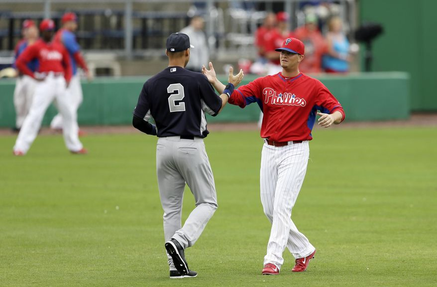 Philadelphia Phillies shortstop Reid Brignac, right, greets New York Yankees shortstop Derek Jeter before an exhibition baseball game Thursday, March 6, 2014, in Clearwater, Fla. (AP Photo/Charlie Neibergall)