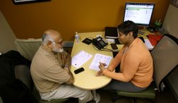 FILE - In this Jan. 9, 2013 file photo, H&R Block Tax preparer Tracey Wales, right, working with customer Muneer Sheikh, on preparing his taxes, at an H&R Block office downtown in Washington. H & R Block reports quarterly earnings on Thursday, March 6, 2014. (AP Photo/Pablo Martinez Monsivais, File)