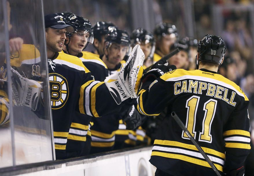 Boston Bruins center Gregory Campbell (11) is congratulated by teammates after his goal against the Washington Capitals during the second period of an NHL hockey game, Thursday, March 6, 2014, in Boston. (AP Photo/Charles Krupa)