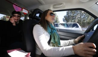 In this Feb. 28, 2014 photo, part time Lyft driver Brittany Cameron drives her own vehicle as she gives a ride to Jennie Morris, left, in downtown Denver. Lyft is a  transportation network company whose mobile-phone application facilitates peer-to-peer ridesharing by enabling passengers who need a ride to request one from drivers who have a car. A dramatic change in the way people hail rides is shaking up decades of regulation now that getting a lift is as easy as making a few taps on a phone. (AP Photo/Brennan Linsley)