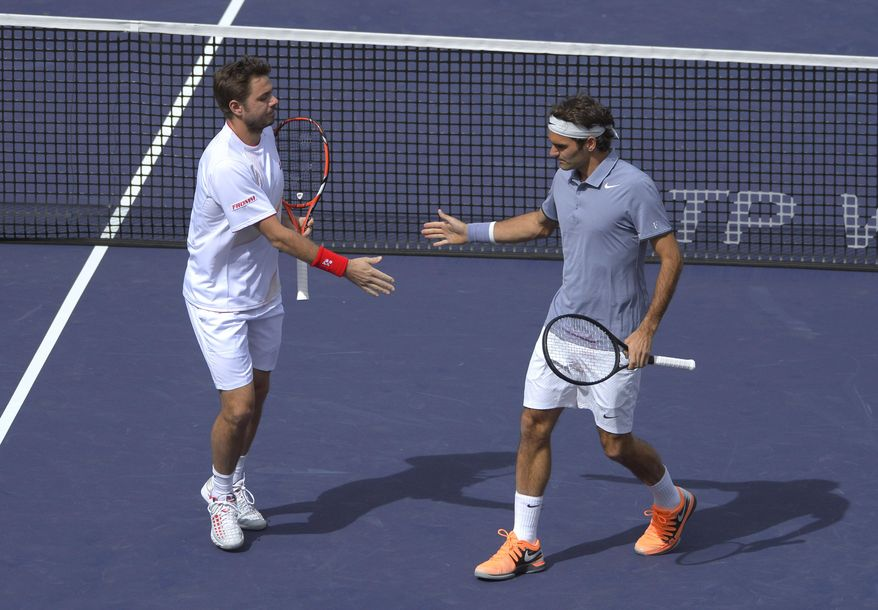 Roger Federer, of Switzerland, right, greets doubles partner Stanislas Wawrinka, of Switzerland, after scoring a point during a match at the BNP Paribas Open tennis tournament against Rohan Bopanna, of India, and Aisam-Ul-Haq Qureshi, of Pakistan,  Friday, March 7, 2014 in Indian Wells, Calif. (AP Photo/Mark J. Terrill)
