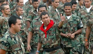 FILE - In this Feb. 7, 2006 file photo, Ramon Isaza, center, commander of the Magdalena Medio Bloc, speaks with his men before turning in their weapons during a disarmament ceremony in Puerto Triunfo, Colombia. Hundreds of right-wing paramilitaries are expected to walk free from prison starting in March 2014 after serving eight-year sentences for crimes that normally carry more than triple the prison terms. Isaza, who is due to be released in October 2014, created the first of the right-wing militias at the end of the 1970s in the Magdalena Valley. (AP Photo/Luis Benavides, File)