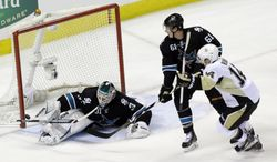 Pittsburgh Penguins' Chris Kunitz (14) scores past San Jose Sharks goalie Antti Niemi (31), of Finland, as Justin Braun (61) watches during the first period of an NHL hockey game on Thursday, March 6, 2014, in San Jose, Calif. (AP Photo/Marcio Jose Sanchez)