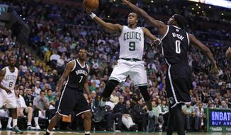 Boston Celtics guard Rajon Rondo (9) drives to the basket between Brooklyn Nets guards Deron Williams (8) and Joe Johnson (7) during the second quarter of an NBA basketball game, Friday, March 7, 2014, in Boston. (AP Photo/Charles Krupa)