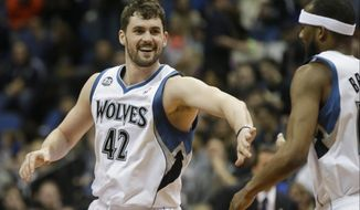 Minnesota Timberwolves' Kevin Love, left, congratulates Corey Brewer after Brewer's dunk in the first quarter of an NBA basketball game against the Detroit Pistons, Friday, March 7, 2014, in Minneapolis. (AP Photo/Jim Mone)
