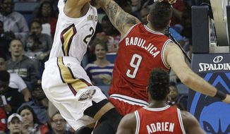 New Orleans Pelicans forward Anthony Davis (23) dunks over Milwaukee Bucks center Miroslav Raduljica (9) as Bucks forward Jeff Adrien (12) watches during the first half of an NBA basketball game in New Orleans, Friday, March 7, 2014. (AP Photo/Bill Haber)