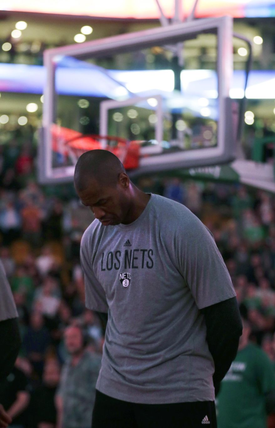 With the stadium lights dimmed, Brooklyn Nets center Jason Collins listens to the national anthem before the Nets faced the Boston Celtics in an NBA basketball game, Friday, March 7, 2014, in Boston. (AP Photo/Charles Krupa)