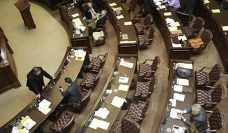 Rep. John K. Hutchison, R-Harrisburg, far left, speaks with Rep. Warwick Sabin, D-Little Rock, lower left, during a recess in the near-empty House chamber at the Arkansas state Capitol in Little Rock, Ark., Friday, March 7, 2014. Budget bills are set to go before the House and Senate next week. (AP Photo/Danny Johnston)