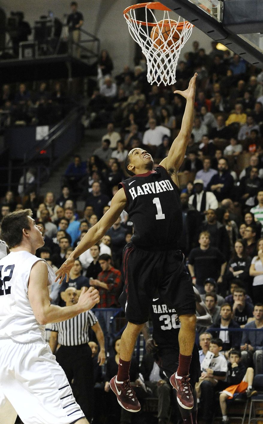 Harvard's Siyani Chambers, right, goes up for a basket as Yale's Matt Townsend, left, defends during the second half of an NCAA college basketball game, Friday, March 7, 2014, in New Haven, Conn. (AP Photo/Jessica Hill)