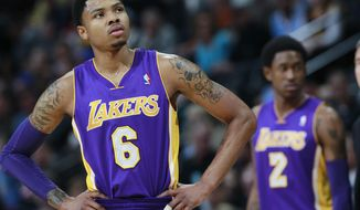 Los Angeles Lakers guard Kent Bazemore, front, looks on against the Denver Nuggets as guard MarShon Brooks, back, checks in to play in the first quarter of an NBA basketball game in Denver on Friday, March 7, 2014. (AP Photo/David Zalubowski)